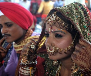 An Indian bride sits with her groom duri